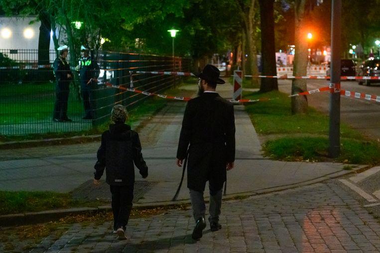 Een jongen en een man lopen naar de synagoge in Hamburg waar de aanslag is gepleegd.  Beeld Jonas Walzberg/dpa