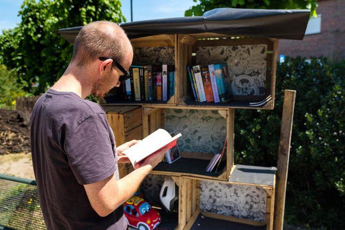 Een lezer komt even wat bladeren in een van de boeken.