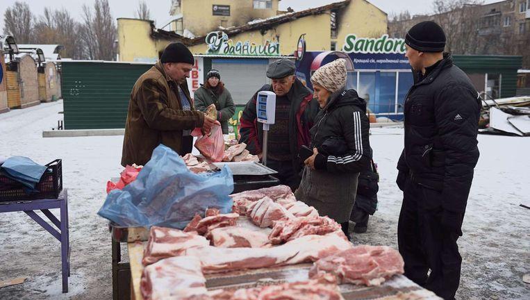 Mensen kopen vlees op een markt in de Oost-Oekraïense stad Donetsk, 2014. Beeld AFP