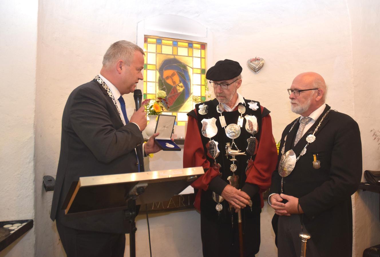 (Vlnr.) Burgemeester Van Stappershoef geeft de penning aan gildekoning Wim van Dijk en hoofdman Jan Kloks.
