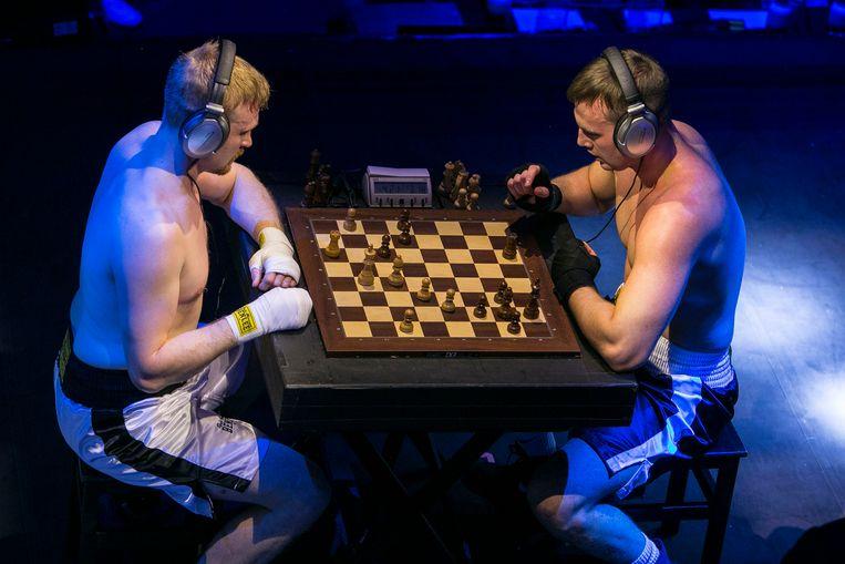 Pro-schaakboksers Dennis Gurba en Sakari Lähderinne. Dat bord tussen het boksen door steeds de ring in en uit is ook best nog een secuur klusje. Beeld Amaury Miller