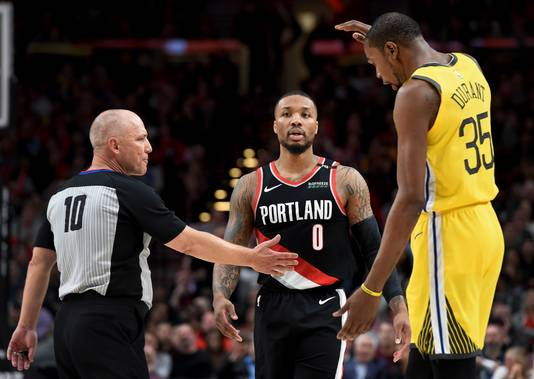 Arbiter Ron Garretson (links) in discussie met Golden State Warriors' Kevind Durant. In het midden Portland Trail Blazers-guard Damian Lillard.