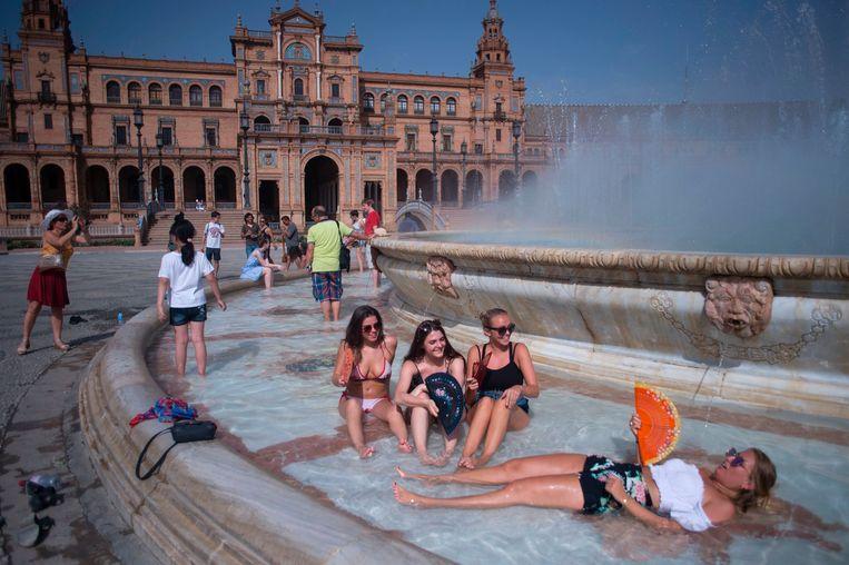 Toeristen zoeken verkoeling in een fontein op de Plaza de Espana in Sevilla.