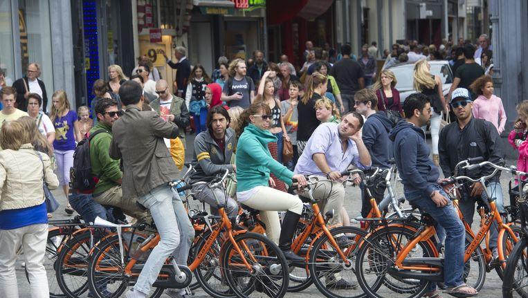 Toeristen met een fiets op de Dam. De grote aantallen toeristen en dagjesmensen staan op de eerste plaats van grootste ergernissen van Amsterdammers. Beeld anp