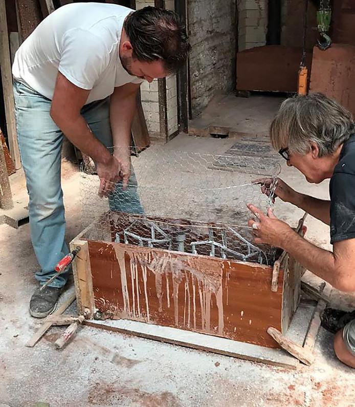 Léon Vermunt (rechts) en Ruben Van de Ven bezig met het maken van de eerste gietmallen voor het kunstwerk d' Ouwe Sok van Roosendaal.