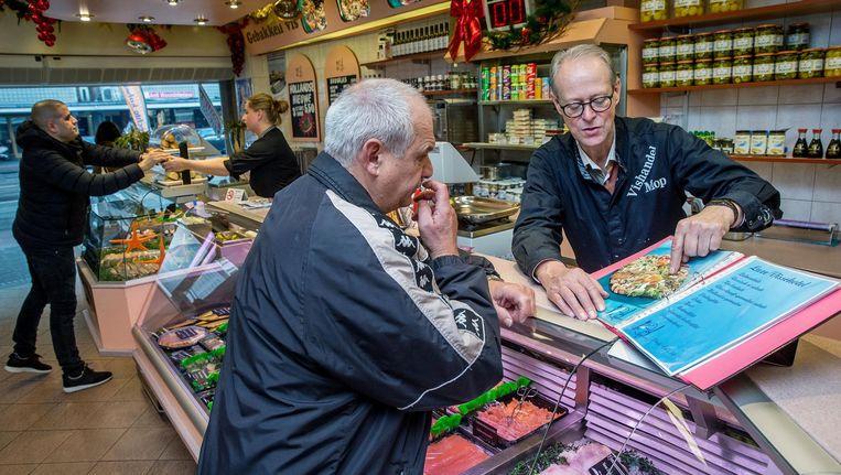 Kees Kwakman helpt een klant op weg in Vishandel Mop in De Baarsjes, een van de oudste van de stad Beeld Jean-Pierre Jans