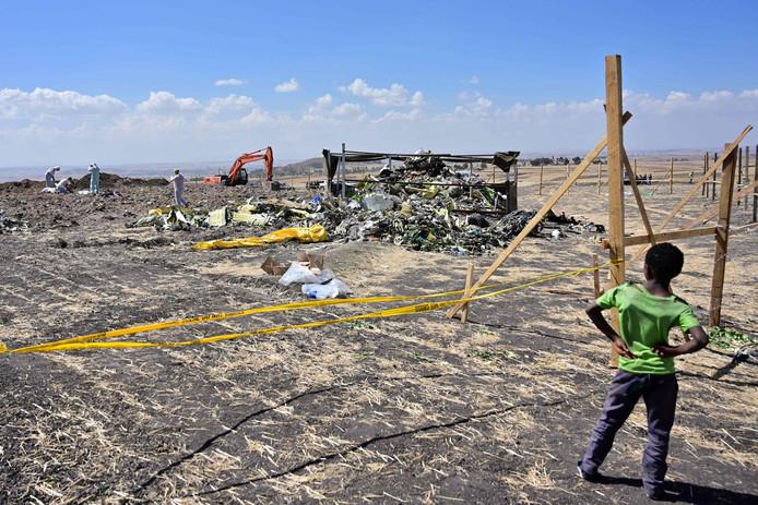 Een jongen kijkt hoe forensisch onderzoekers door het puin gaan van de gecrashte Boeing 737 MAX van Ethiopian Airlines.