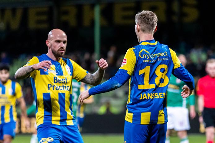 Bryan Smeets (l) feliciteert rechtsback Dennis Janssen met zijn doelpunt, dat TOP Oss hielp aan de overwinning bij FC Dordrecht.