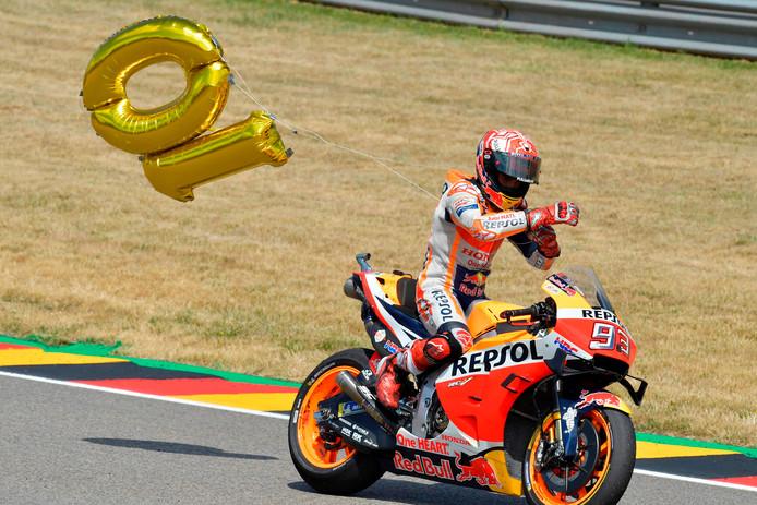 Marquez rijdt na zijn zege rond met een ballon met het getal 10.