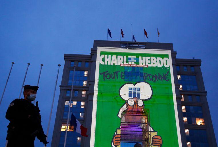 Een Franse politieman staat naast een gebouw in Montpellier waarop een spotprent uit het satirische tijdschrift Charlie Hebdo wordt geprojecteerd. Het is een eerbetoon aan de vermoorde leraar Samuel Paty. Beeld EPA