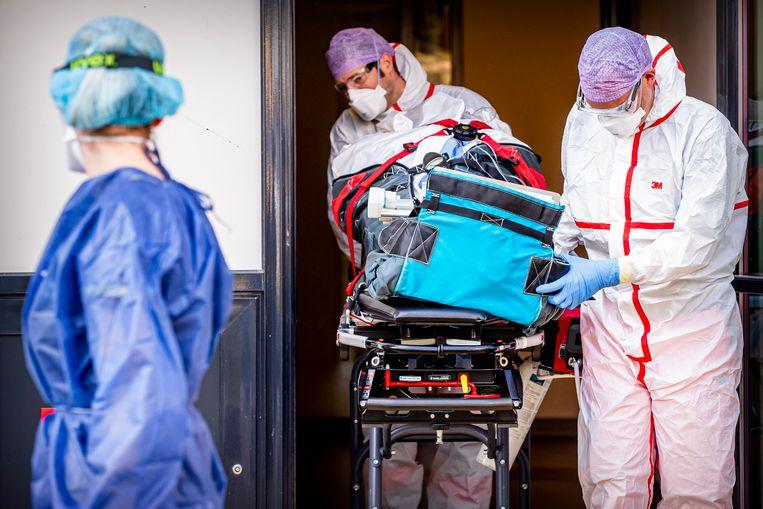 Een coronapatiënt wordt in Den Bosch naar een helikopter gebracht die hem naar Duitsland brengt, waar meer plek is op de intensive care.  Beeld Getty Images