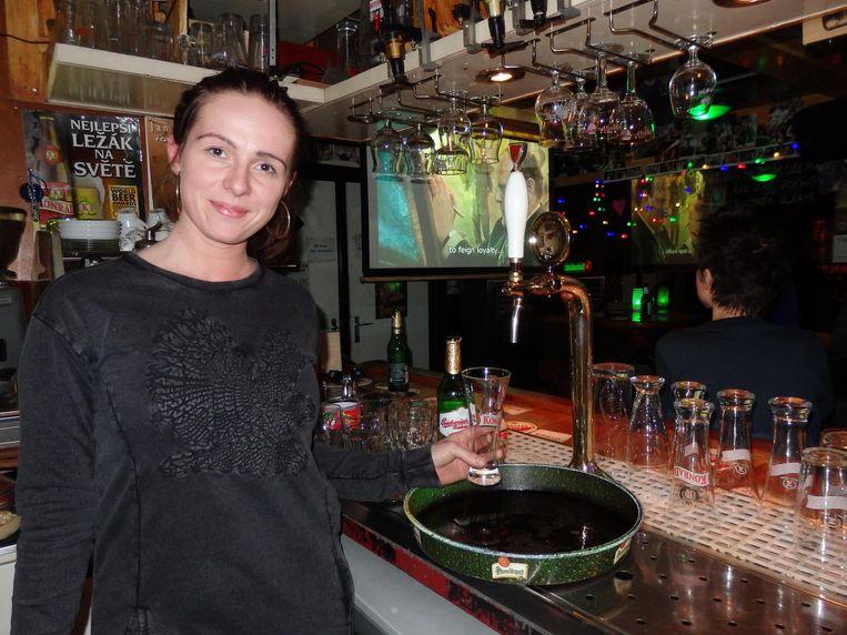 Barvrouw Lívia Blahutová met Tsjechisch bier van de tap. Ze schenkt ook Becherovka Beeld Schuim
