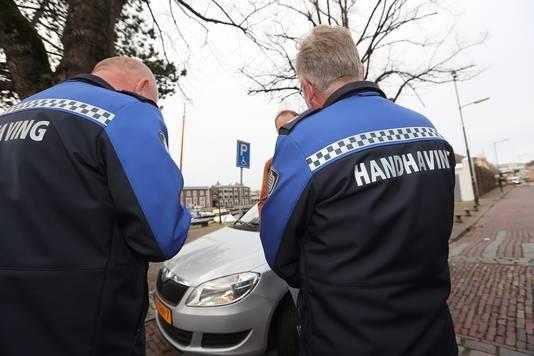 Stadswachten delen een bekeuring uit aan een automobilist.