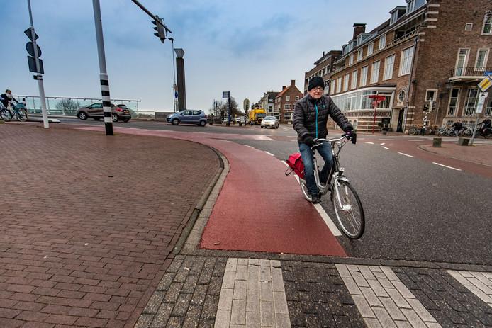 Het probleem in beeld: wie met de fiets vanaf de Stadsbrug in Kampen komt (links op de foto) en rechtsaf de IJsselkade op wil, krijgt te maken met een scherpe bocht. Veel fietsers komen nét op het zwarte asfalt en fietsen dan over de gladde witte lijnen.