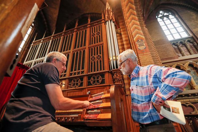 Nico van Duren en Nico van Dongen (rechts) bij het 100 jaar oude orgel in de Sint Joriskerk in Eindhoven.