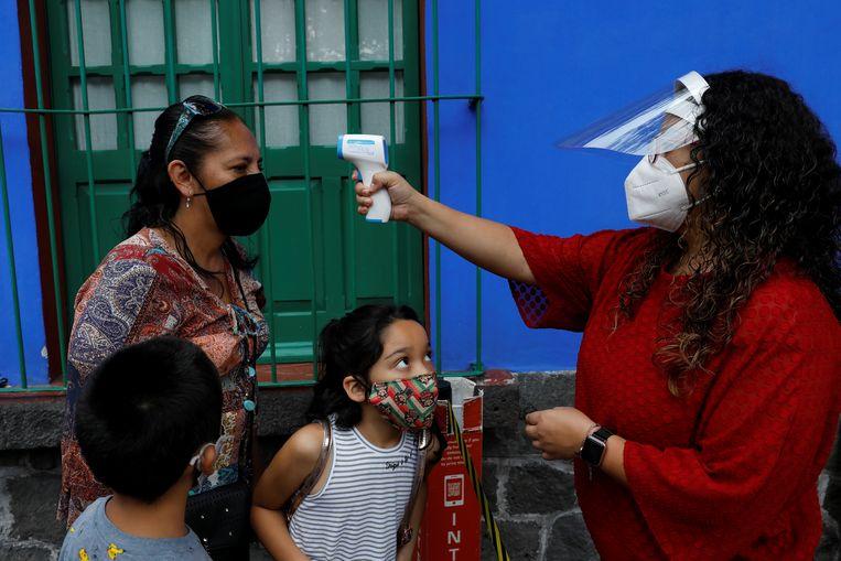 Temperatuurcontrole van een familie die het Frida Kahlo Museum in Mexico-Stad wil betreden.  Beeld REUTERS