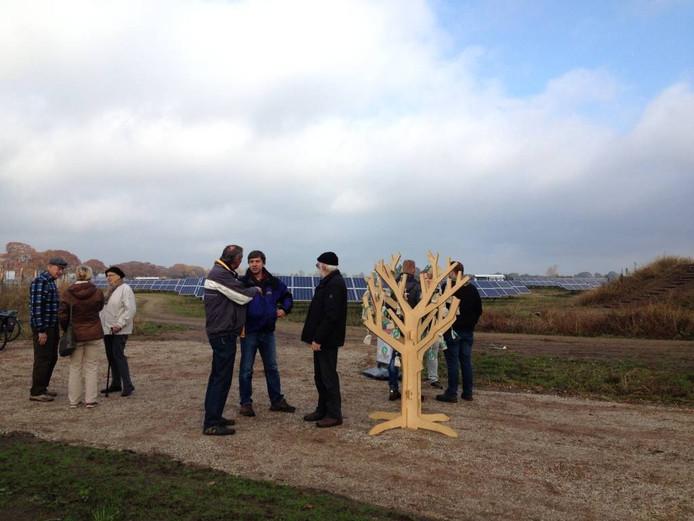 Bezoekers praten over het grote solarpark, op de achtergrond zichtbaar. Foto DG