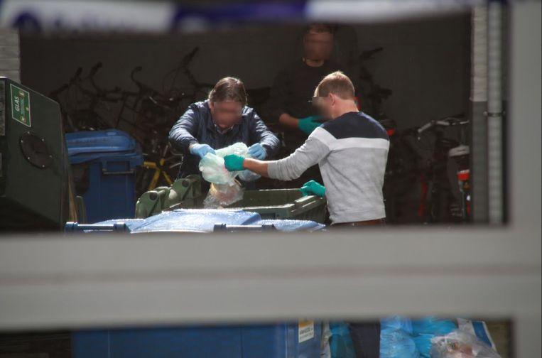 Speurders doorzoeken de vuilnisbakken in het gebouw.