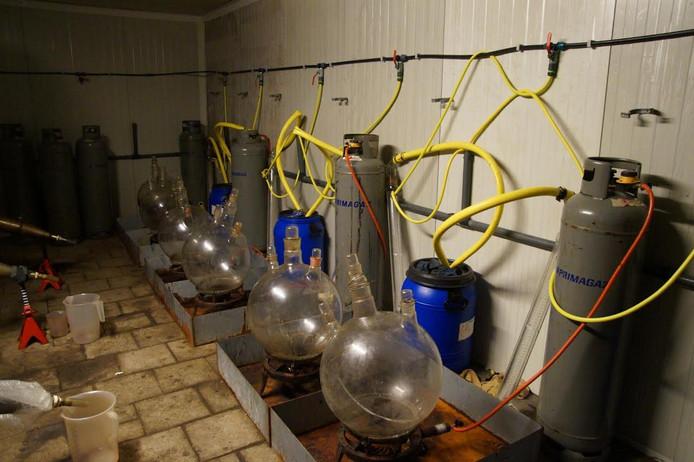 Een loods vol vaten, flessen en chemische apparatuur.