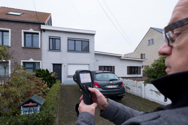 Guido Verlinden richt de warmtecamera op de gevel van een woning om het energieverlies te meten.