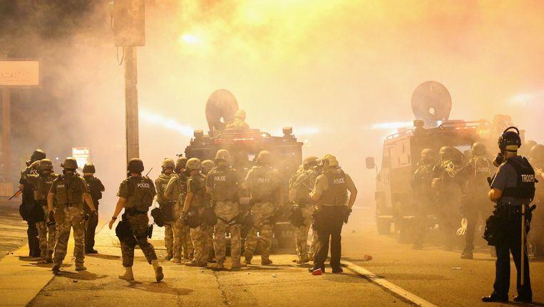 De politieagenten trekken de straat in door een wolk van traangas heen. Beeld getty