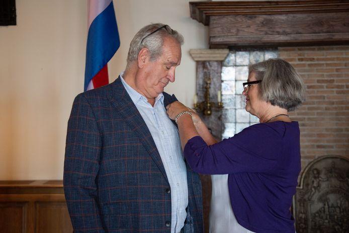 Peet Bakx krijgt het lintje opgespeld door zijn vrouw, Brigit.