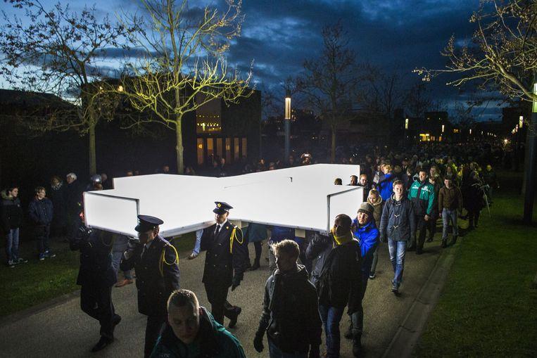Mensen dragen voor The Passion een groot verlicht kruis door de straten van Enschede. Beeld anp