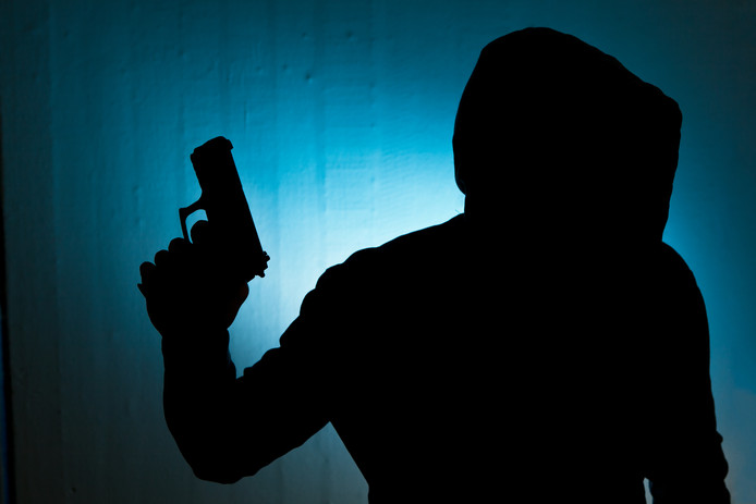 Silhouetted man with gun against blue wall background overval criminaliteit wapen pistool