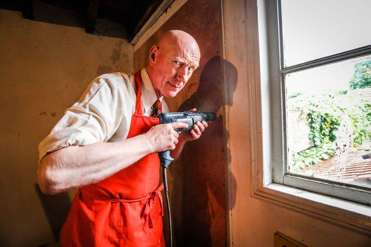 Herr Seele sluit de deur, langs waar de inbreker vermoedelijk kwam, af met een houten plank en schroeven.