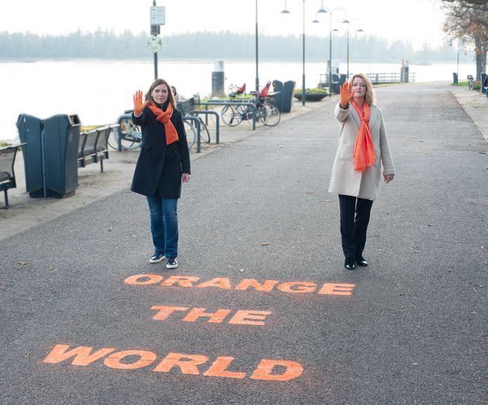 Wike van den Bout (links) en Reinie Melissant spoten de tekst Orange the World op de weg bij Buiten de Waterpoort in Gorinchem.