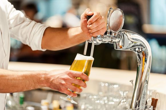 Close-up of young bartender pouring beer while standing at the bar counter