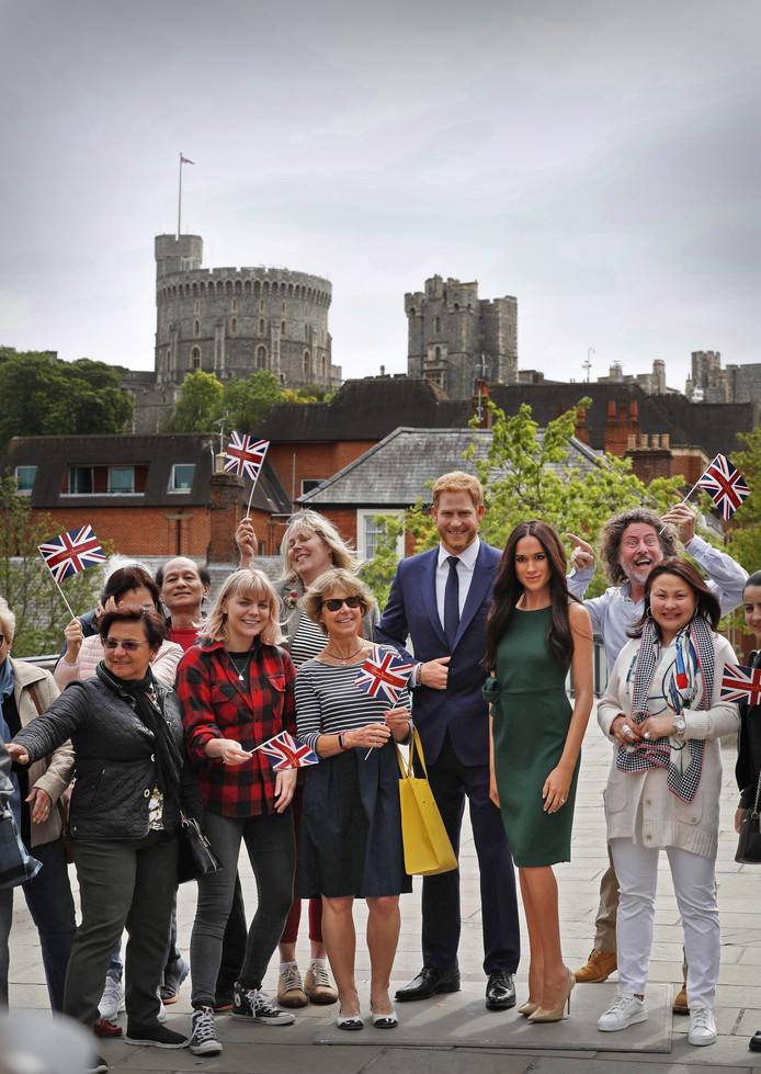 Bezoekers aan Windsor poseren bij het kasteel met wassen beelden van prins Harry en Meghan Markle.