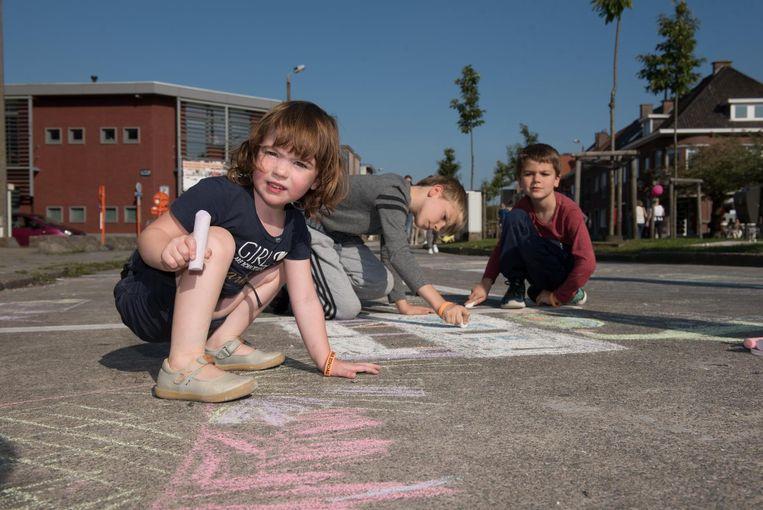 Deze kinderen maken een krijttekening op straat.