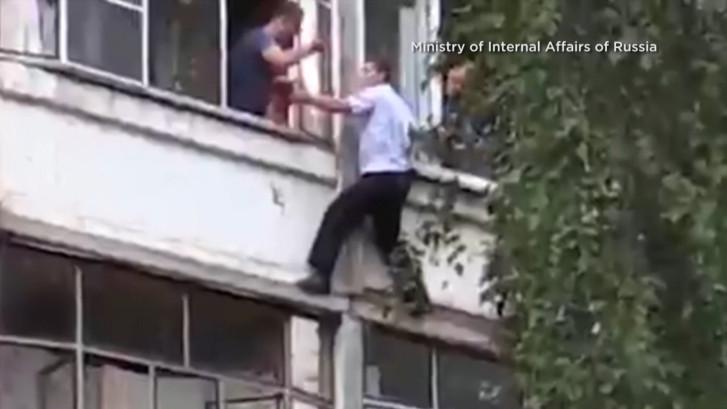 Un père menace de lâcher sa fille d'une fenêtre, un policier héroïque l'en empêche
