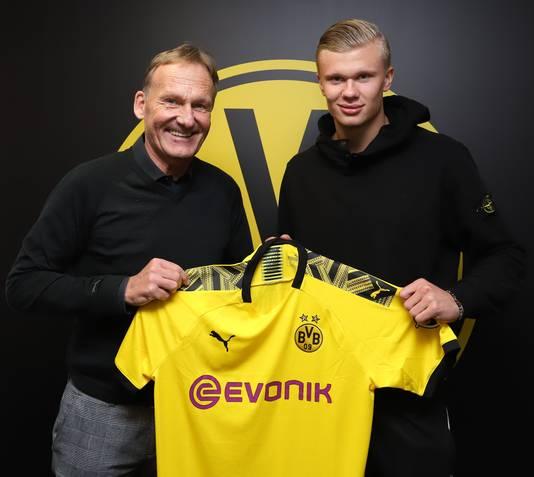 Haaland poseert met het Dortmund shirt, geflankeerd door de CEO van Dortmund; Hans-Joachim Watzke.