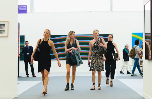 Deze vrouwen op de Frieze Art Fair hebben hun telefoon in de aanslag, op zoek naar iets wat ze optilt