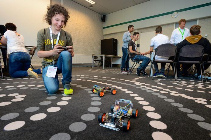 Geamuseerd bestuurt Noah Willemsen bij Aeronamic een robocar met een smartphone.