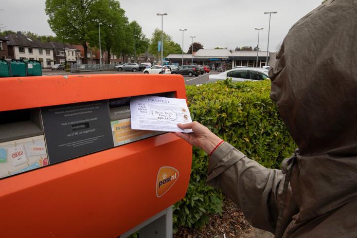 Nanny van Hese stopt de brief voor de burgemeester van Deurne in een brievenbus in Geldrop. Ze heeft haar metalen jas aan die straling tegenhoudt.