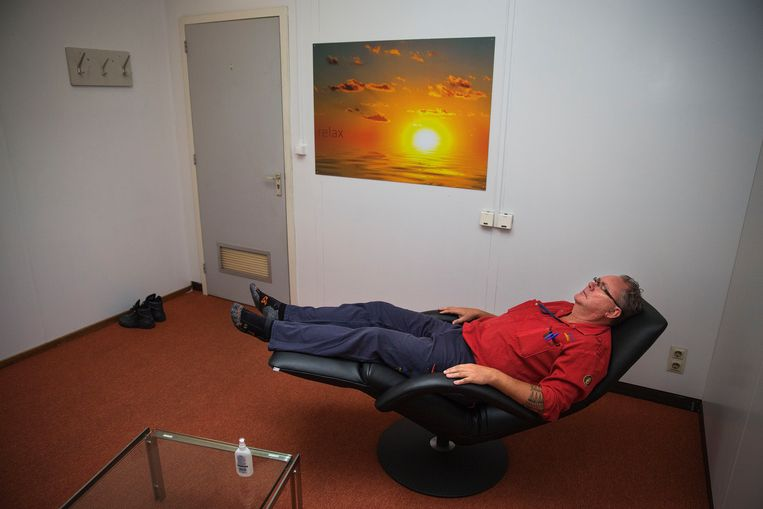 Een medewerker van een petrochemisch bedrijf doet een powernap op het werk.  Beeld Arie Kievit / Hollandse Hoogte