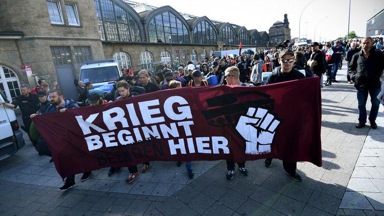 Demonstranten komen aan bij het treinstation in Hamburg met een spandoek waarop staat: 'De oorlog begint hier'. Beeld EPA