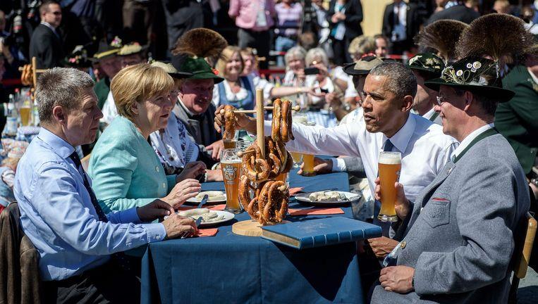 De Duitse bondskanselier Angela Merkel genoot afgelopen zondag met de Amerikaanse president Barack Obama van een traditioneel Beiers ontbijt-met-bier tijdens de G7-top. Nadat Merkel een foto van deze gebeurtenis op Instagram had geplaatst, kwamen direct Russische trollen in actie. Beeld epa