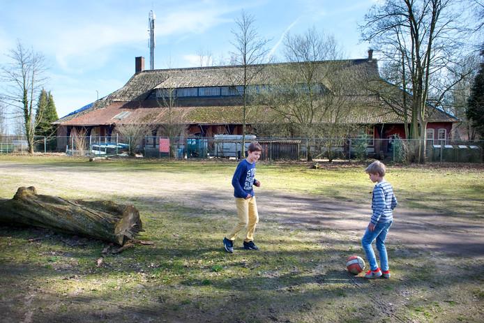Kinderen vermaken zich op de parkeerplaats van SC EDS in Ellecom, met op de achtergrond de monumentale SS-sporthal.