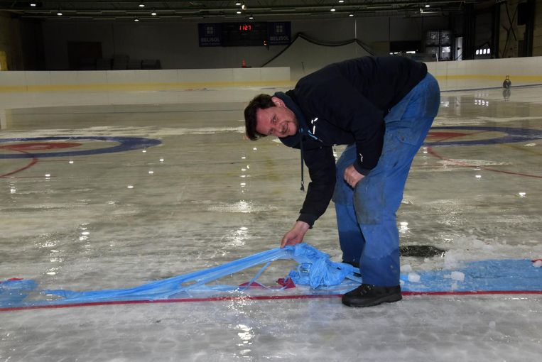 Hans Van Accom ruimt de belijning van de ijsbaan op.