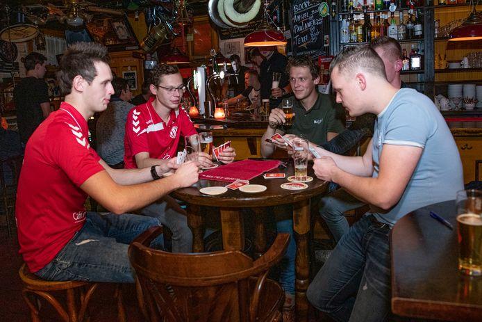 Mike Huberts (groene shirt)  legt een kaartje met zijn vrienden in kroeg de Kastelein. Afgelopen week was het café wereldnieuws.