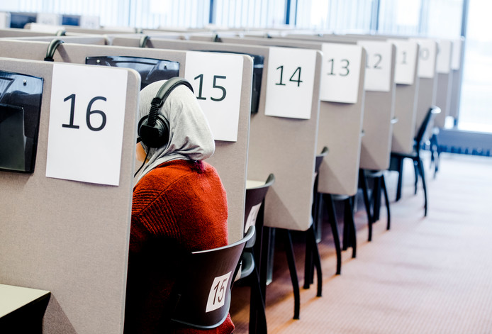 Een mevrouw maakt een inburgeringsexamen op een toetslocatie van Dienst Uitvoering Onderwijs (DUO). Foto ter illustratie.