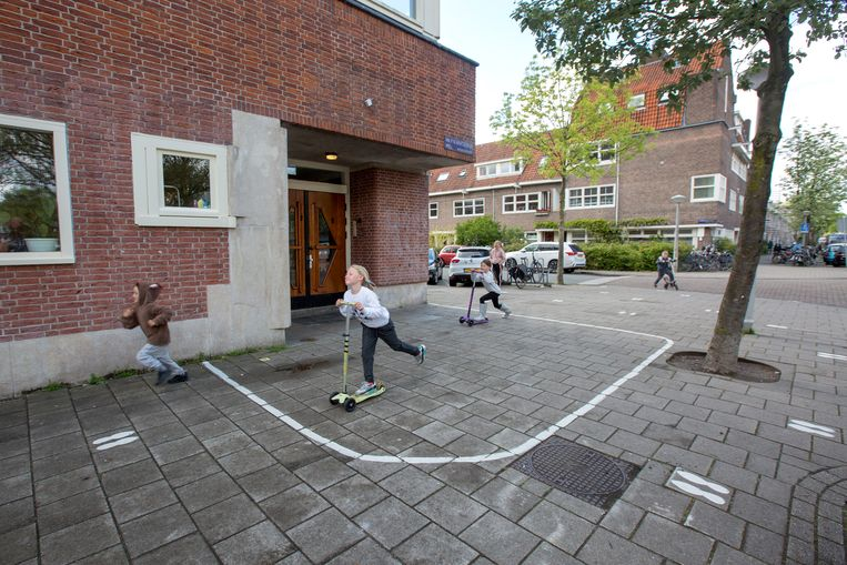 Op de grond voor de ingang van basisschool de Watergraafsmeerse Schoolvereniging in Amsterdam zijn vast lijnen en voetstappen geplaatst zodat ouders weten hoe groot de afstand is die ze moeten houden als ze kinderen halen en brengen. Beeld Maartje Geels