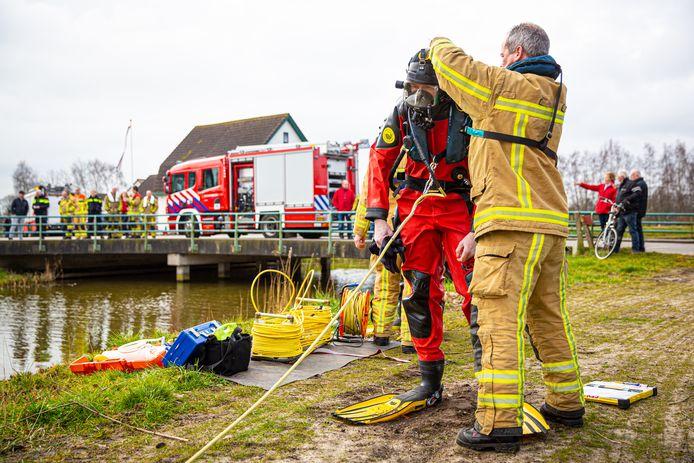 Een duiker van de brandweer Heerde wordt aangekleed om het water in te gaan.