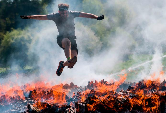 Een deelnemer aan de jaarlijkse Viking-race in Stockholm springt over een brandend obstakel. Foto Jonathan Nackstrand