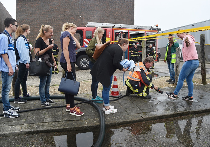 De voeten van medewerkers van Albert Heijn worden door de brandweer afgespoten om verspreiding van asbest te voorkomen.