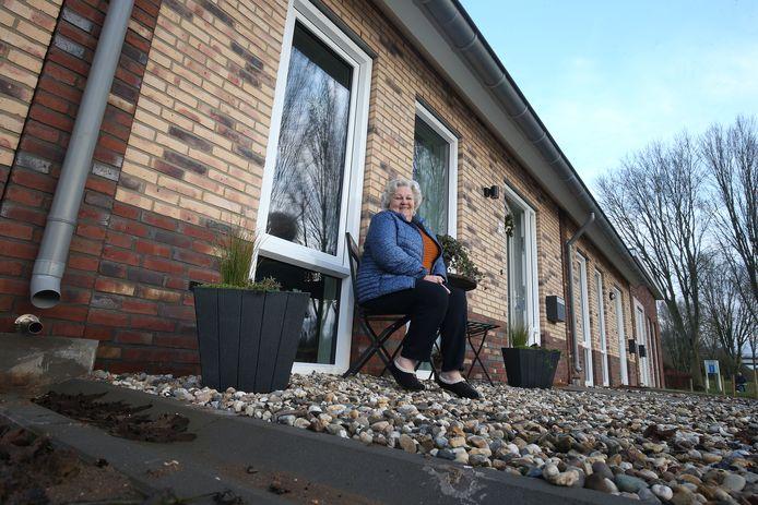 Betsy Teerink in haar voortuin, met gootje voor het afvoeren van regenwater.